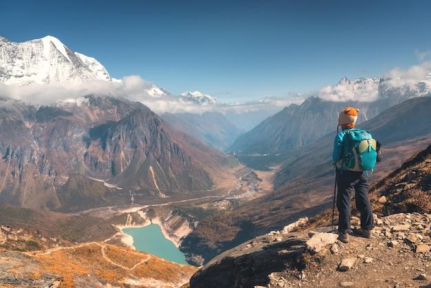 Mulher em pé contra um belo lago e montanhas