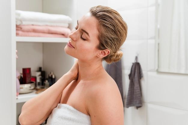 Mulher em pé de toalha com os olhos fechados