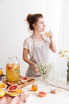 Mulher em pé dentro de casa bebendo bebida cítrica