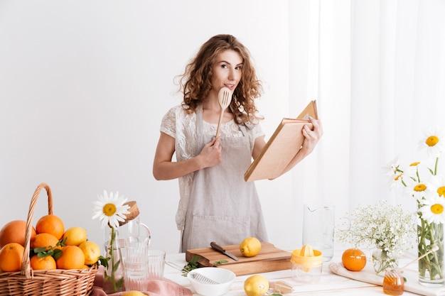 Mulher em pé dentro de casa perto da mesa com muitos cítricos