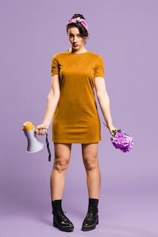 Mulher em pé e segurando o megafone e flores
