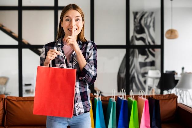 Mulher em pé e segurando um saco de papel