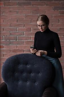 Mulher em pé e usando o celular