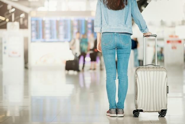 Mulher em pé em um aeroporto com bagagem