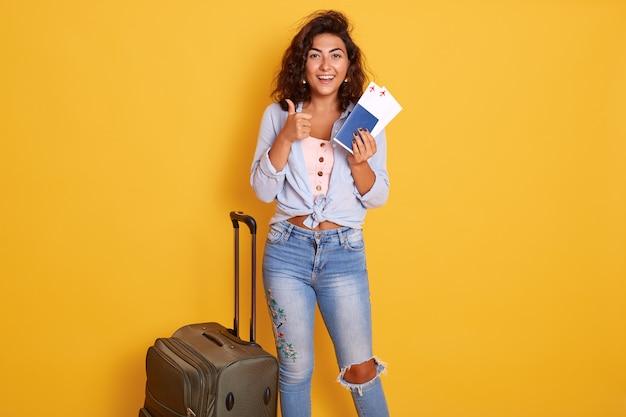 Mulher em pé isolado sobre fundo amarelo, segurando o passaporte e passagem,