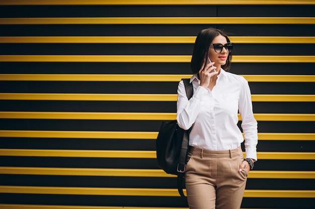 Mulher em pé junto à parede amarela e falando ao telefone