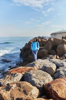 Mulher em pé na costa do oceano atlântico, ondas violentas atingindo a costa, o surf