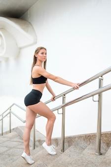 Mulher em pé na escada e olhando para longe