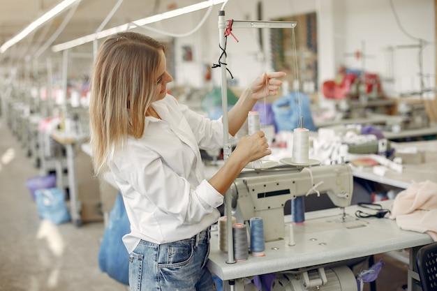 Mulher em pé na fábrica com um fio