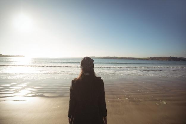 Mulher em pé na praia durante o dia