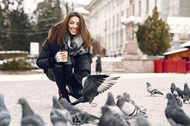 Mulher em pé na rua cercada de pombos