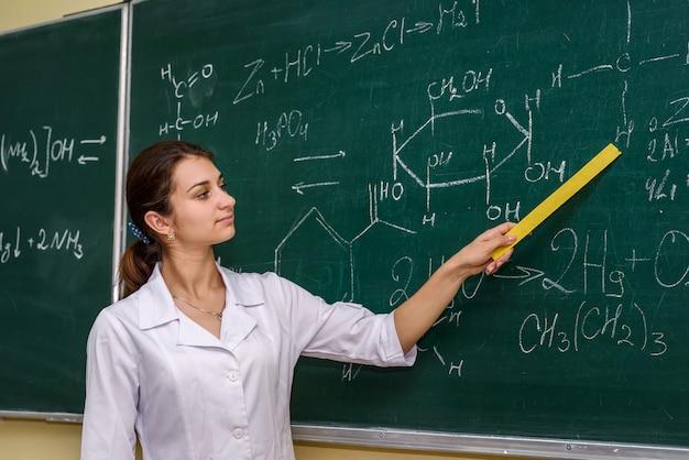 Mulher em pé na sala de aula de químico perto do quadro e apontando para ele