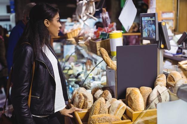 Mulher em pé no balcão de pão