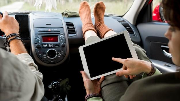 Mulher em pé no banco do passageiro usando um tablet perto do namorado