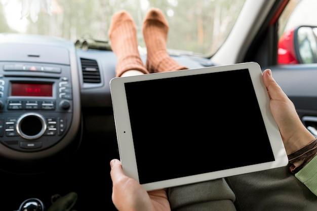 Mulher em pé no banco do passageiro usando um tablet