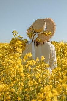 Mulher em pé no campo de colza, vista traseira, por trás no verão