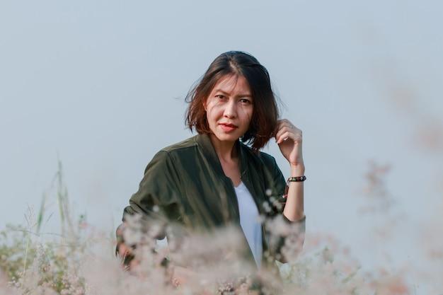 Mulher em pé no campo de grama com cabelos balançando