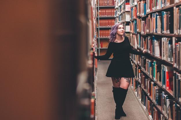 Mulher em pé no meio de estantes