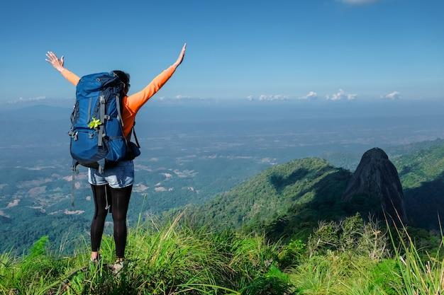 Mulher em pé no penhasco e empurre as mãos contra a montanha e a árvore