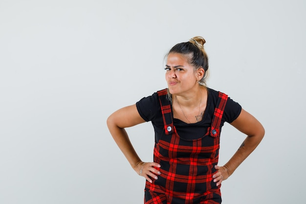Mulher em pé para ouvir claramente em um vestido avental e parecendo curiosa, vista frontal.