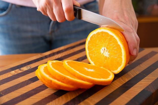 Mulher em pé perto da mesa e cortar laranja em fatias