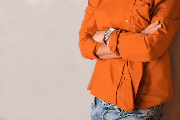 Mulher em pé perto da parede com os braços cruzados