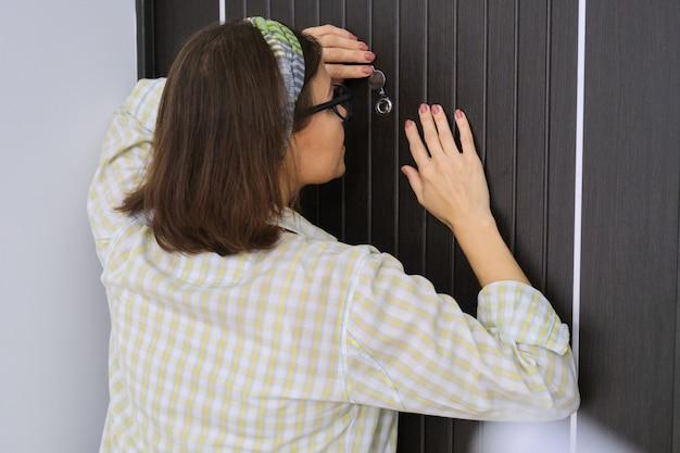 Mulher em pé perto da porta da frente, olhando pelo olho mágico