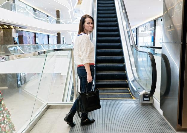 Mulher em pé perto de uma escada rolante