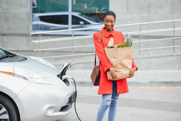 Mulher em pé perto do carro. senhora com produtos alimentares.