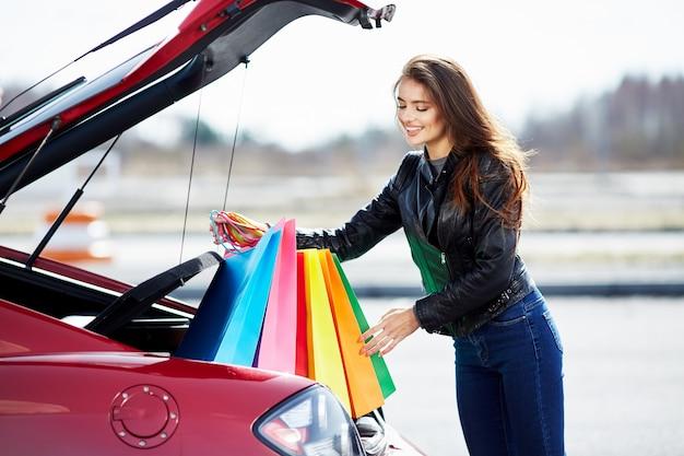 Mulher em pé perto do carro vermelho, motorista feliz. mulher olhando para baixo e sorrindo, fora do carro. mulher feliz colocando sacolas coloridas depois de fazer compras no carro