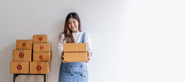 Mulher em pé segurando caixas de encomendas, proprietária de uma loja online, verificando pedidos, caixas de encomendas para embalagem de mercadorias, envio por meio de uma empresa de correio privado. venda online e conceitos de compras online.