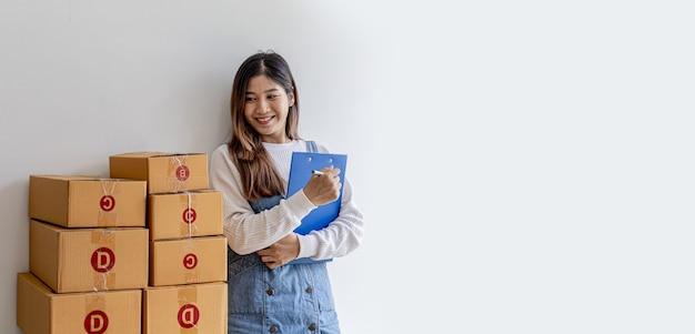 Mulher em pé segurando pastas, dona de uma loja online verificando pedidos, caixas de encomendas para embalagem de mercadorias, remessa por meio de uma empresa de courier privada. venda online e conceitos de compras online.