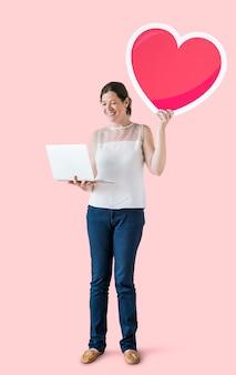 Mulher em pé, segurando um emoticon de coração e um laptop