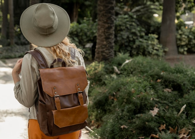 Mulher em plano médio com chapéu andando na natureza