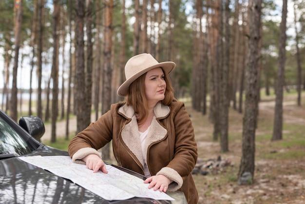 Mulher em plano médio com mapa e carro