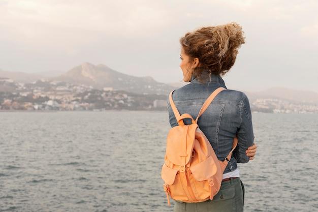 Mulher em plano médio com mochila à beira-mar