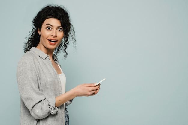 Mulher em plano médio com telefone e cópia-espaço
