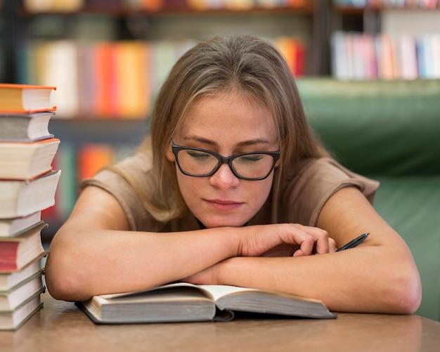Mulher em plano médio estudando na biblioteca