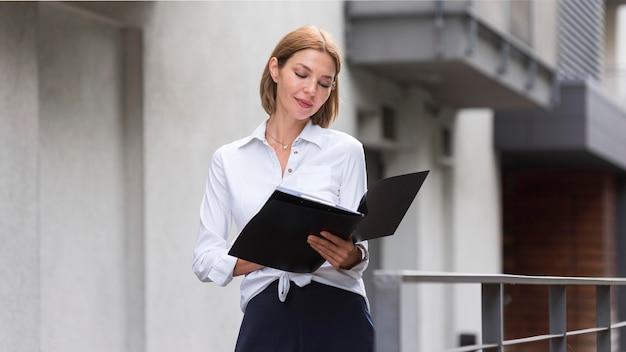 Mulher em plano médio olhando documentos