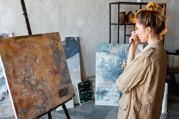 Mulher em plano médio olhando para uma pintura