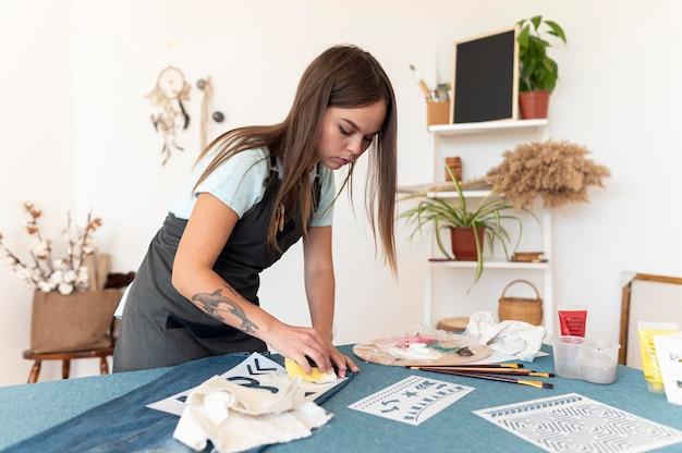 Mulher em plano médio pintando com esponja