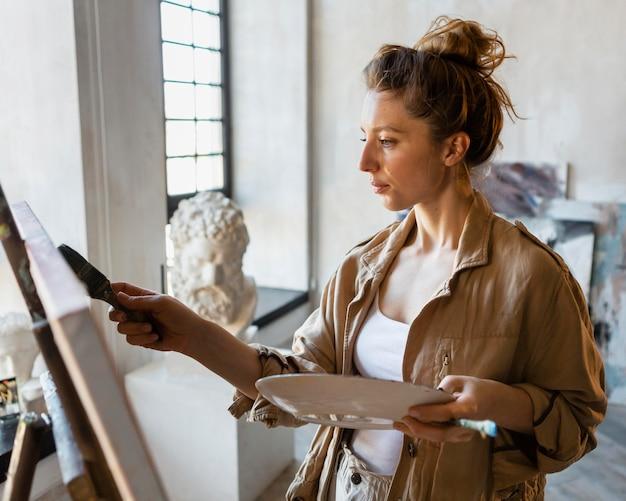 Mulher em plano médio pintando dentro de casa