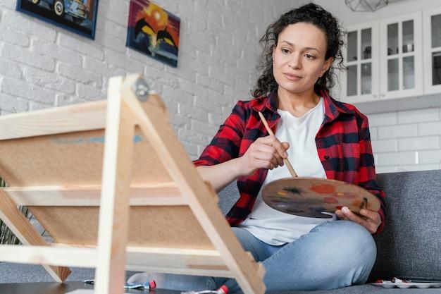 Mulher em plano médio pintando em casa
