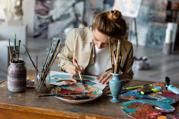 Mulher em plano médio pintando na mesa