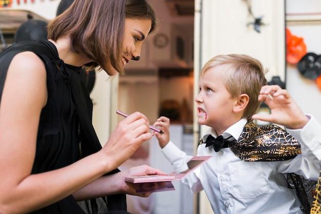 Mulher em plano médio pintando rosto de criança