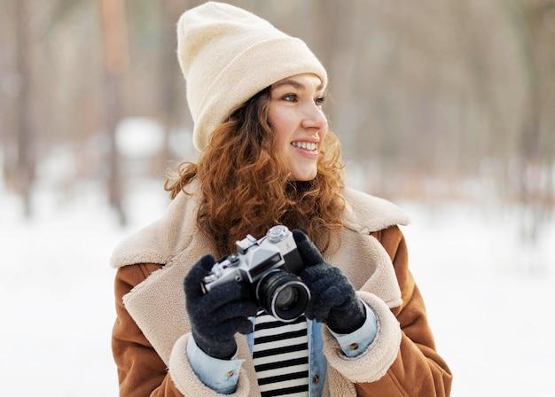 Mulher em plano médio segurando a câmera