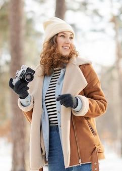 Mulher em plano médio segurando uma câmera fotográfica