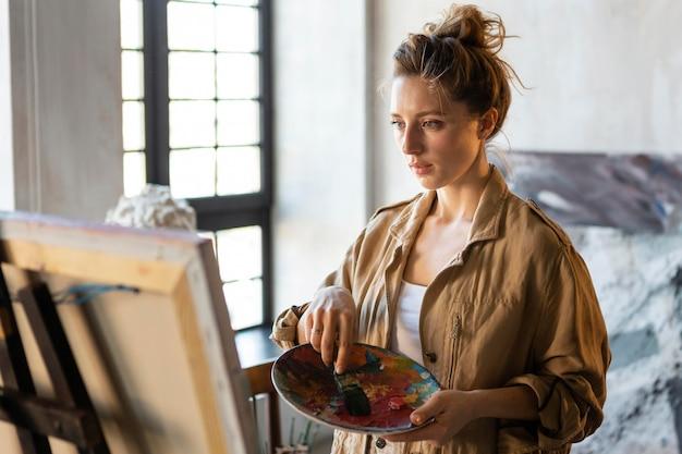 Mulher em plano médio segurando uma paleta de pintura