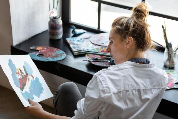 Mulher em plano médio segurando uma pintura