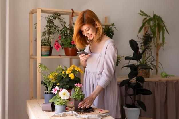 Mulher em plano médio tirando fotos com o telefone